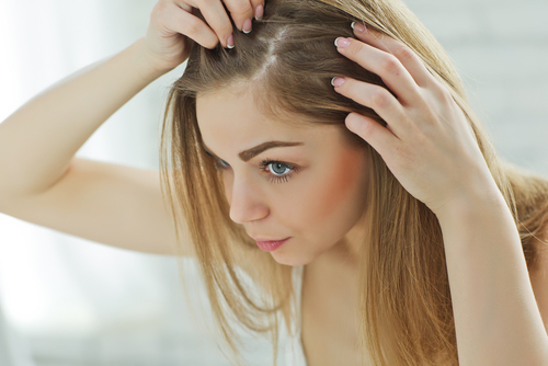 woman inspecting her hair