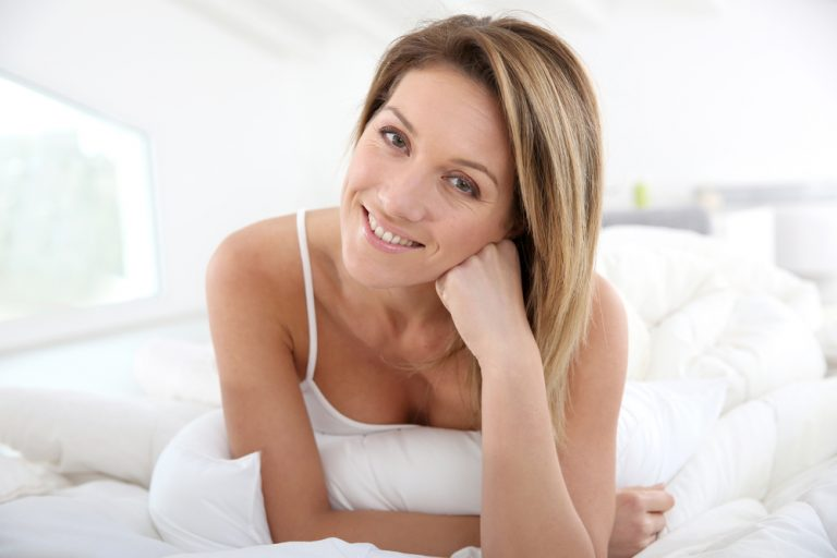 woman wearing white while posing with hand resting on chin