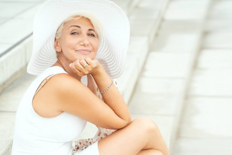 mature woman smiling while wearing large hat